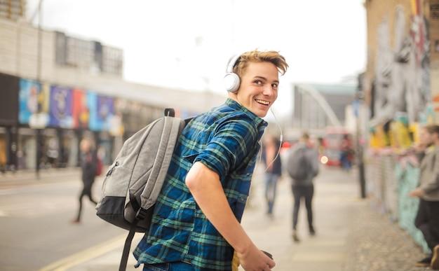 Hübscher kerl, der in die straße während hörende musik mit kopfhörern läuft Premium Fotos