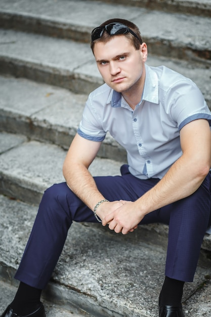 Hübscher kerl im blauen hemdsitzen Premium Fotos