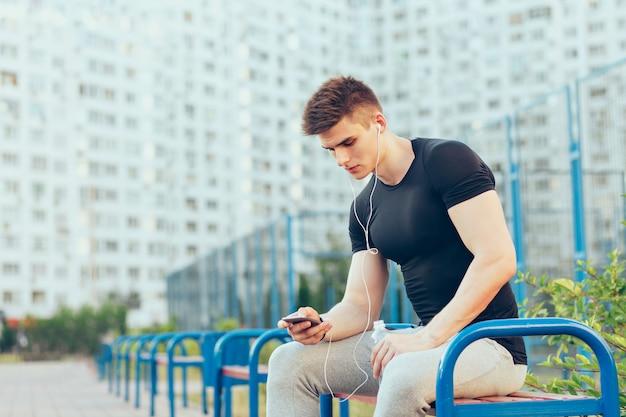 Hübscher kerl im sportschwarz-t-shirt und in der grauen sporthose sitzt auf bank auf stadt- und stadionhintergrund. er tippt am telefon und hört musik über kopfhörer. Kostenlose Fotos