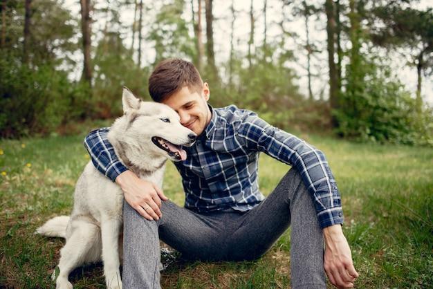 Hübscher kerl in einem sommerpark mit einem hund Kostenlose Fotos