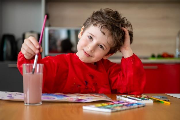 Hübscher kleiner junge, der bilder zu hause zeichnet Premium Fotos