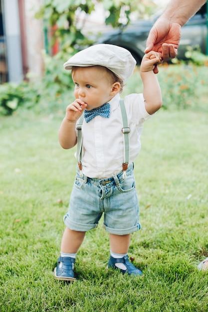Hübscher kleiner kaukasischer junge in stilvoller kleidung geht mit den eltern zum garten Premium Fotos