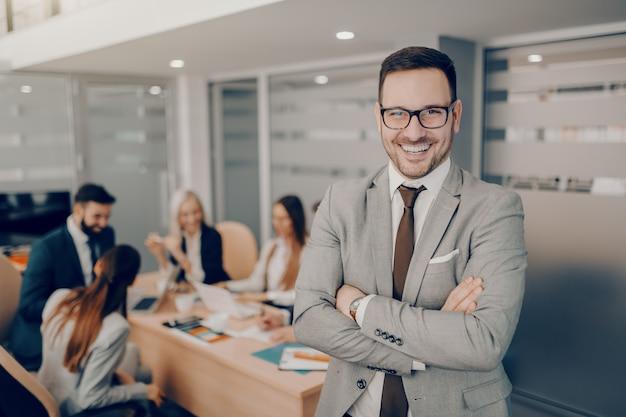 Hübscher lächelnder geschäftsmann in der formellen abnutzung und in den brillen, die im sitzungssaal mit verschränkten armen stehen. liebe und respekt gehen nicht automatisch mit einer führungsposition einher. Premium Fotos