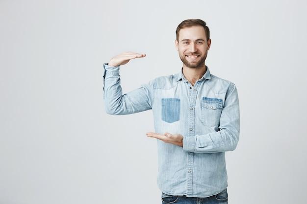 Hübscher lächelnder mann, der größe von etwas großem zeigt Kostenlose Fotos
