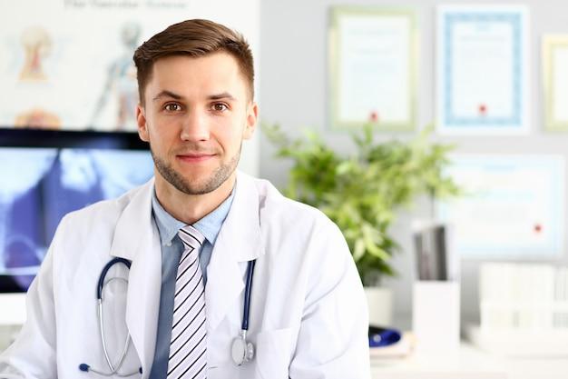Hübscher lächelnder medizindoktor, der im büro sitzt Premium Fotos