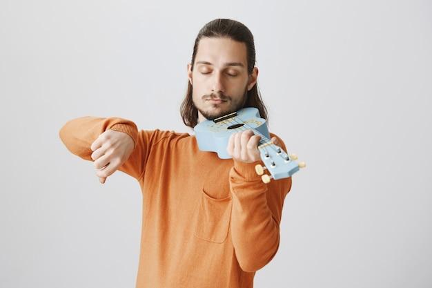 Hübscher lustiger kerl, der ukulele wie geige hält Kostenlose Fotos