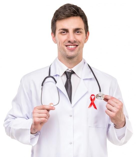 Hübscher männlicher doktor mit rotem band als symbol von aids. Premium Fotos