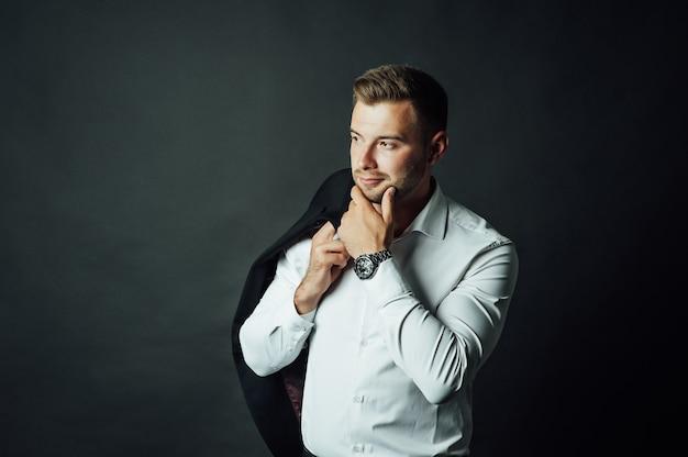 Hübscher männlicher geschäftsmann mit anzug, der in einem fotostudio aufwirft. porträt in halber länge Premium Fotos