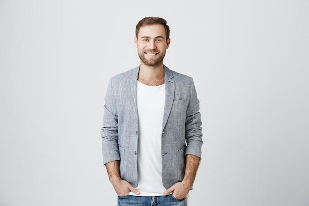 Hübscher männlicher unternehmer, der fröhlich lächelt Kostenlose Fotos