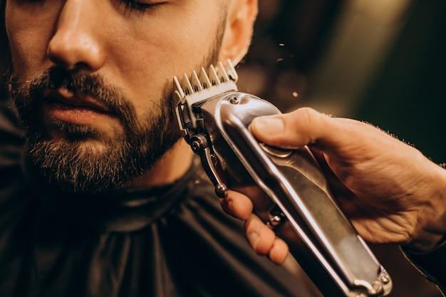 Hübscher mann am friseursalon, der bart rasiert Kostenlose Fotos