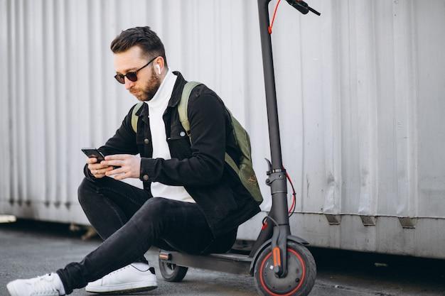 Hübscher mann auf roller, der online am telefon einkauft Kostenlose Fotos