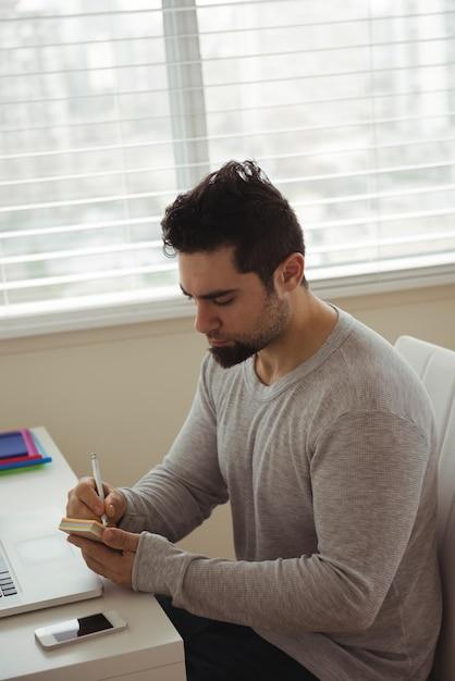 Hübscher mann, der auf haftnotiz schreibt Kostenlose Fotos
