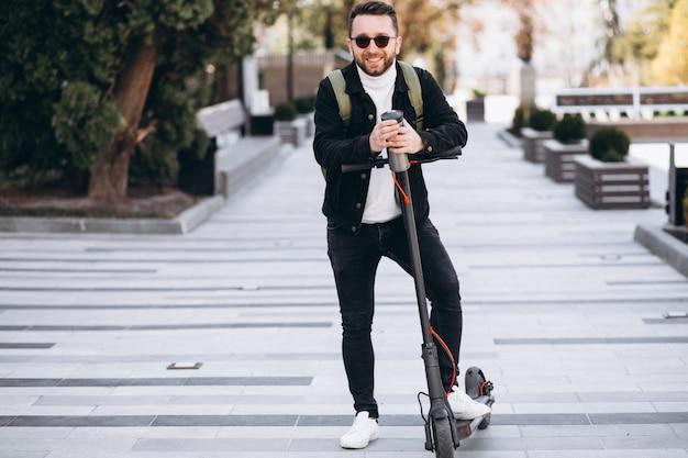 Hübscher mann, der auf roller reitet und kaffee von der thermoskanne trinkt Kostenlose Fotos