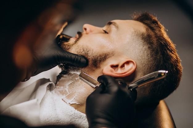 Hübscher mann, der bart an einem friseursalon schneidet Kostenlose Fotos