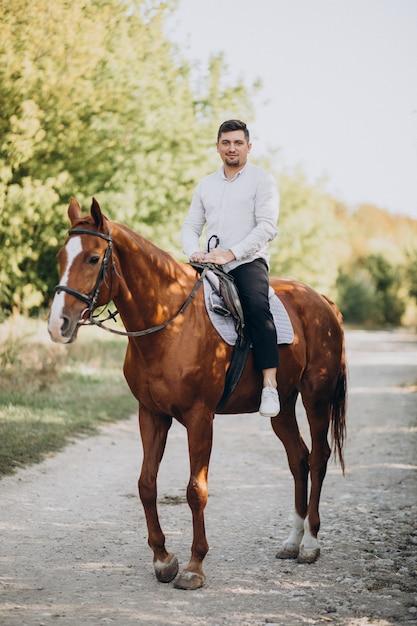 Hübscher mann, der ein pferd im wald reitet Kostenlose Fotos
