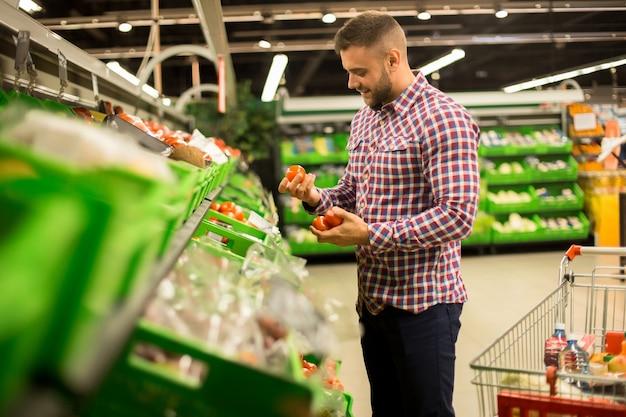 Hübscher mann, der frische tomaten im supermarkt wählt Premium Fotos