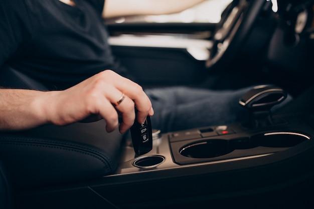 Hübscher mann, der im auto sitzt und es testet Kostenlose Fotos