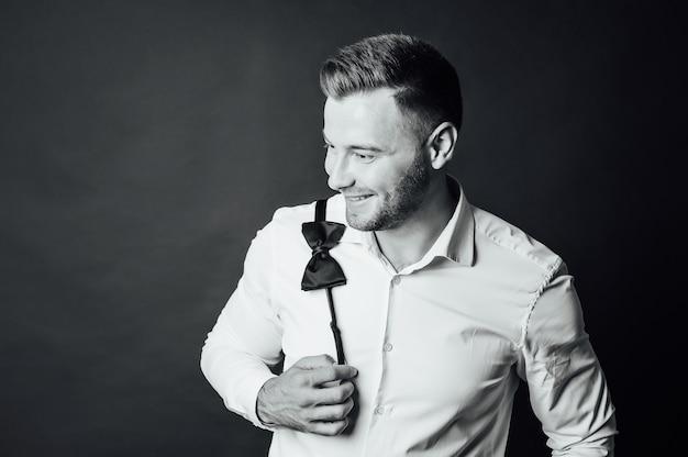 Hübscher mann im weißen hemd hält eine fliege auf seiner schulter Premium Fotos