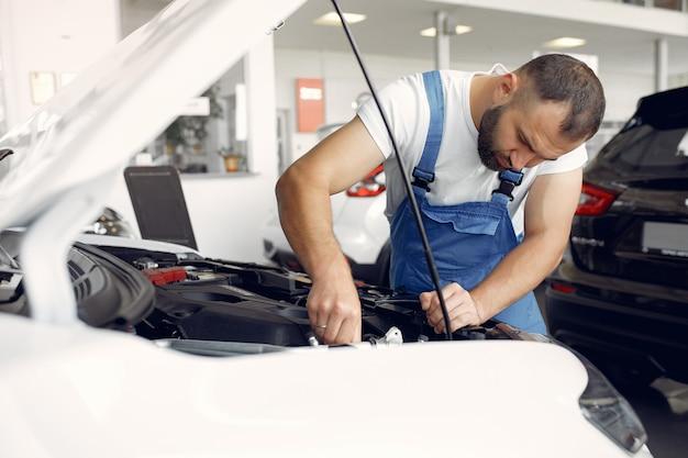 Hübscher mann in blauer uniform überprüft das auto Kostenlose Fotos
