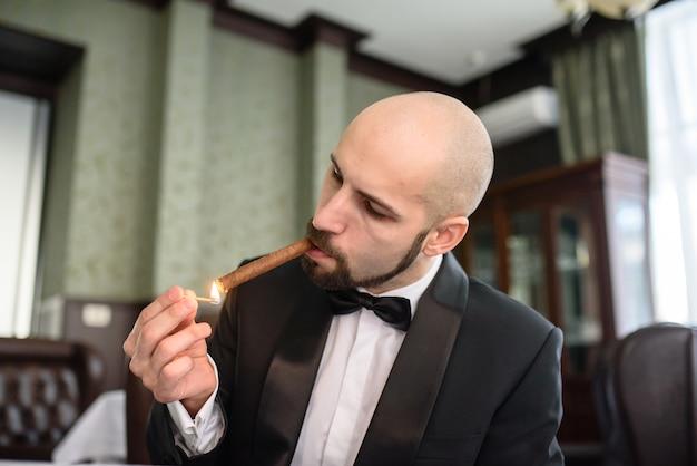 Hübscher mann in einem frack raucht eine zigarre Premium Fotos