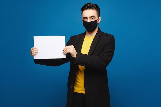 Hübscher mann in einer schwarzen schutzmaske, die ein leeres blatt papier hält und in die kamera schaut, lokalisiert auf den blauen hintergrund. werbekonzept. gesundheitskonzept Premium Fotos