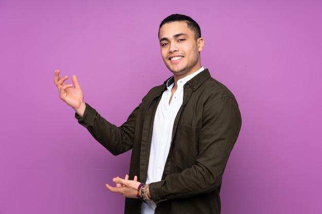 Hübscher mann lokalisiert auf blauer wand, die hände zur seite ausstreckt, um einzuladen, zu kommen Premium Fotos