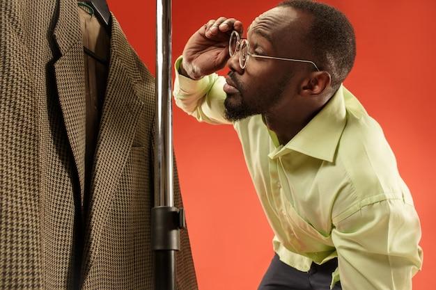 Hübscher mann mit bart, der hemd in einem geschäft wählt Kostenlose Fotos