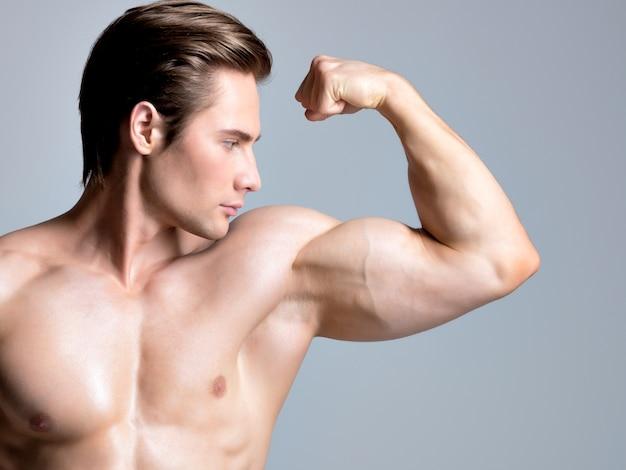 Hübscher mann mit sexy muskulösem schönen körper, der aufwirft Kostenlose Fotos