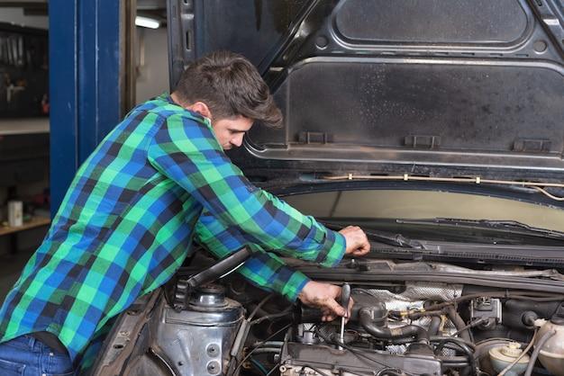 Hübscher mechaniker, der am telefon bei der reparatur eines autos spricht. Premium Fotos