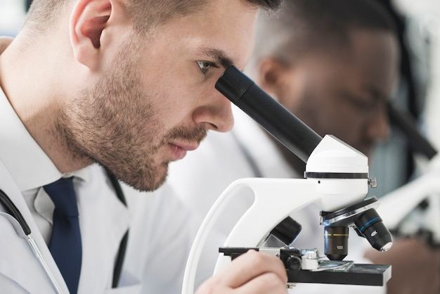 Hübscher mediziner, der mikroskop betrachtet Kostenlose Fotos