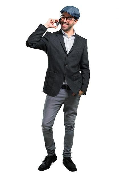 Hübscher moderner mann mit barett und gläsern sprechend mit mobile Premium Fotos