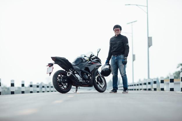 Hübscher motorradfahrer mit sturzhelm in den händen des motorrades Kostenlose Fotos