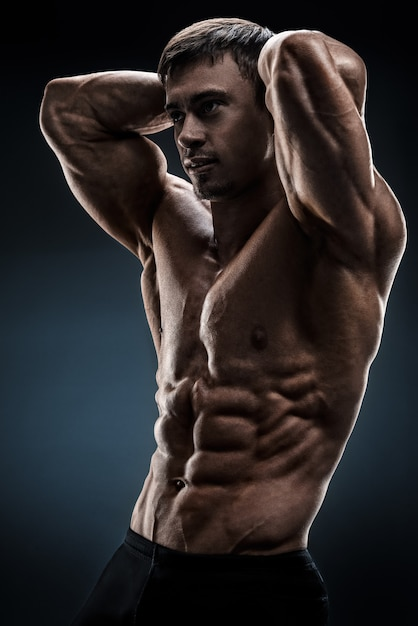 Hübscher muskulöser bodybuilder, der über schwarzem hintergrund aufwirft Premium Fotos