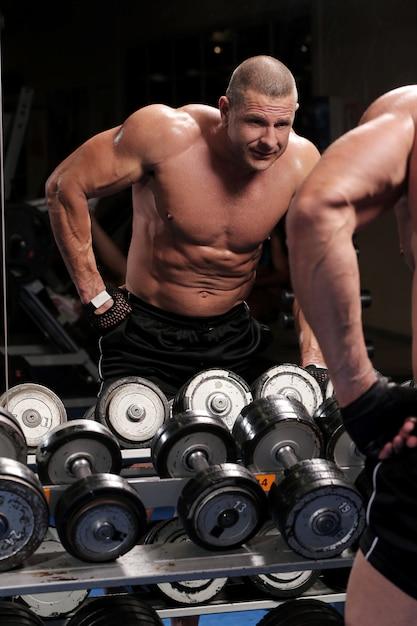 Hübscher muskulöser mann an einer turnhalle Kostenlose Fotos