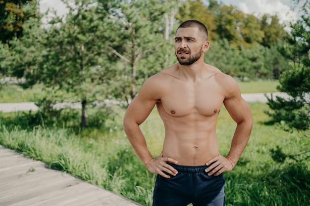 Hübscher muskulöser mann mit nacktem oberkörper im freien