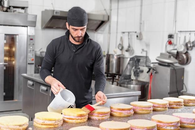 Hübscher professioneller konditor, der einen stapel köstlichen kuchen in der konditorei macht. Premium Fotos