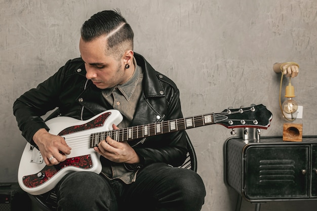 Hübscher rocker, der e-gitarre spielt Kostenlose Fotos