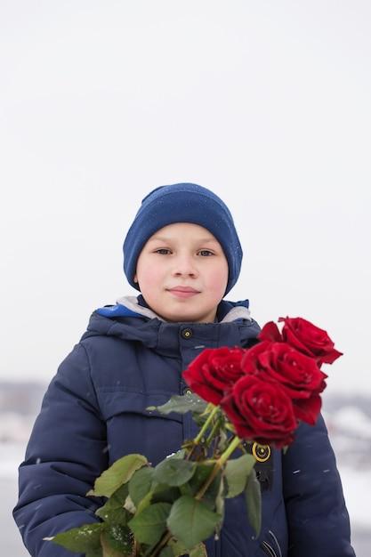 Hübscher romantischer junger mann mit strauß roter rosen in den händen Premium Fotos