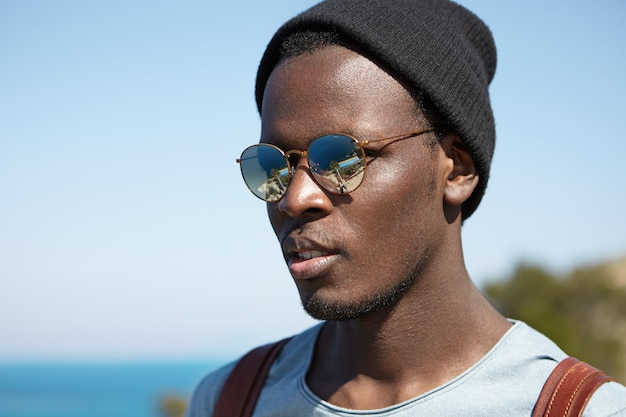 Hübscher schwarzer junger hipster, der stilvollen hut und runde sonnenbrille mit verspiegelter linse trägt und schöne und glückliche momente seiner reise in ein fremdes land bewundert, während er alleine um die welt reist Kostenlose Fotos
