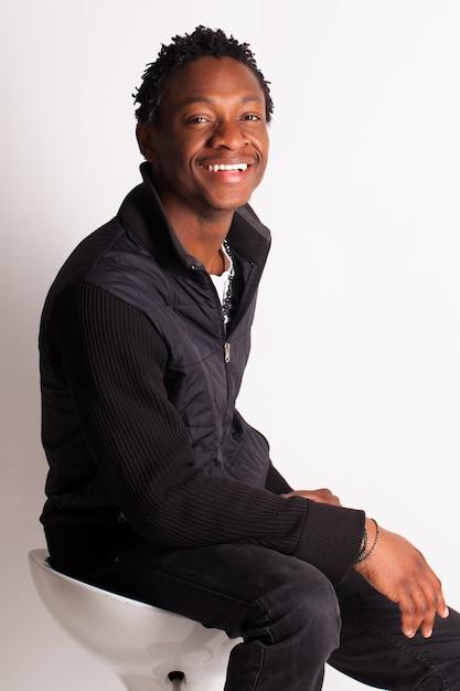 Hübscher schwarzer kerl, der auf einem stuhl sitzt Kostenlose Fotos