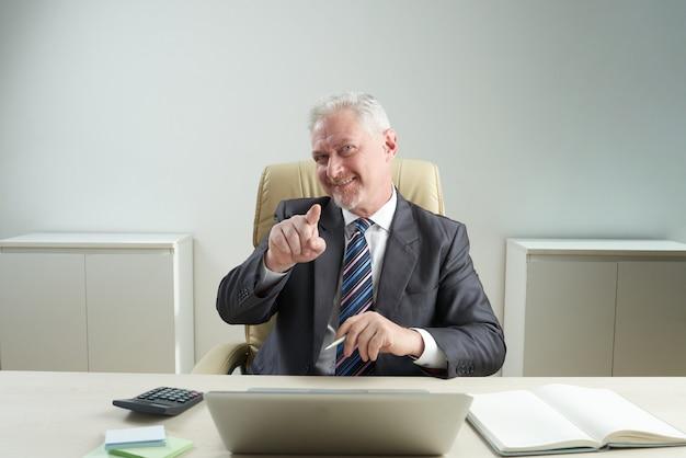 Hübscher senior manager, der auf kamera zeigt Kostenlose Fotos