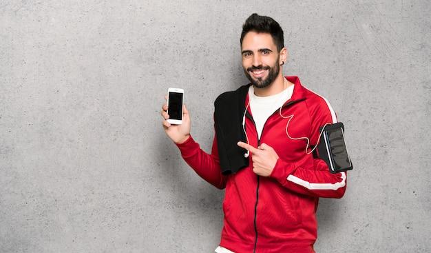 Hübscher sportler, der das mobile über strukturierter wand glücklich und gezeigt worden sein würden Premium Fotos