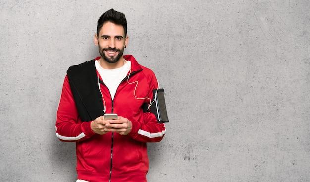 Hübscher sportler, der eine mitteilung mit dem mobile über strukturierter wand sendet Premium Fotos