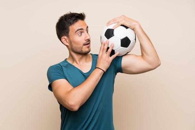 Hübscher sportmann über dem lokalisierten hintergrund, der einen fußball hält Premium Fotos