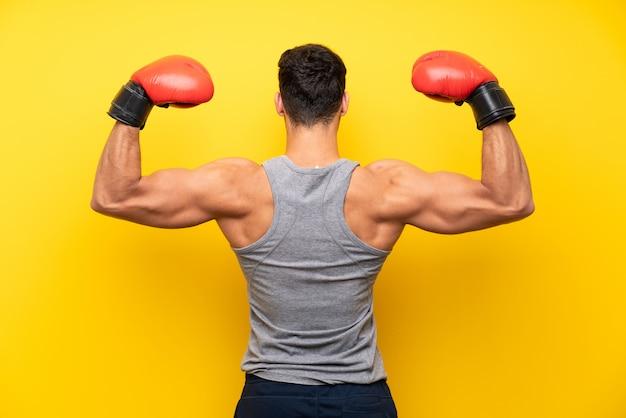 Hübscher sportmann über lokalisiertem hintergrund mit boxhandschuhen Premium Fotos