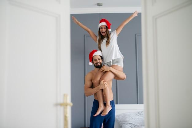 Hübscher starker hemdloser mann mit weihnachtsmütze, der seine freundin auf einer schulter im schlafzimmer hält. Premium Fotos