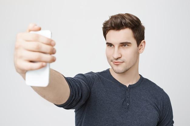 Hübscher stilvoller mann, der selfie für soziale medien auf smartphone nimmt Kostenlose Fotos