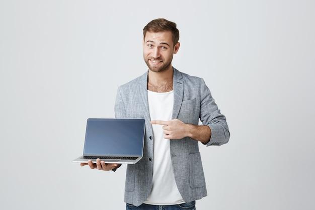 Hübscher stilvoller unternehmer, der auf laptop-anzeige zeigt Kostenlose Fotos