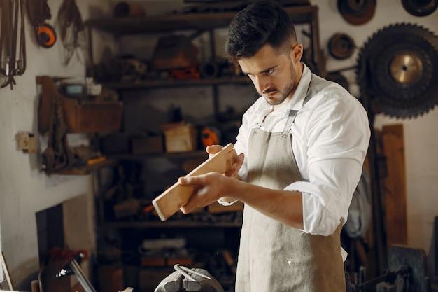 Hübscher tischler, der mit einem holz arbeitet Kostenlose Fotos
