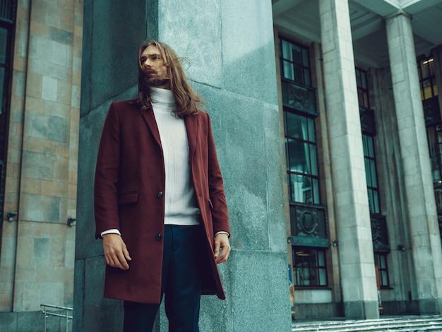 Hübscher überzeugter gut gekleideter mann mit dem bart, der weg draußen schauen aufwirft. modernes reiches männliches modell im roten wintermantel und in der weißen strickjacke Kostenlose Fotos